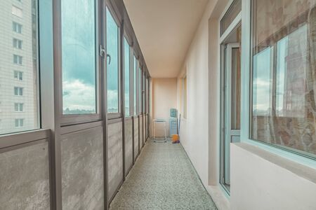 Small old common open balcony interior in high residential apartment building maid of cement Archivio Fotografico
