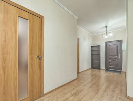 Empty residential house entrance with closed wooden doors tiny hallway