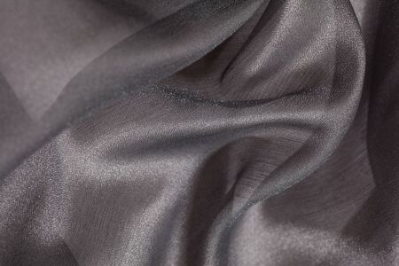 Shiny cloth background with grey vial textile multiple curls