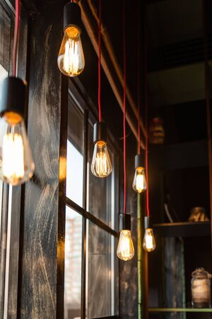 retro warm light bulbs hang at different levels along the window. red wire wooden window