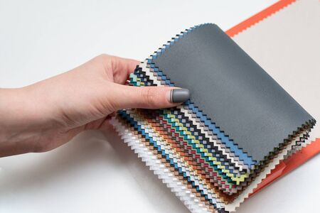 multicolored textile samples catalog for selection female hand white background Stock Photo