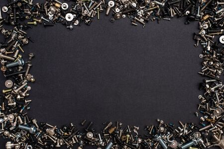 Many different screws and nuts of different sizes and colors. equipment repair. frame, black surface Standard-Bild