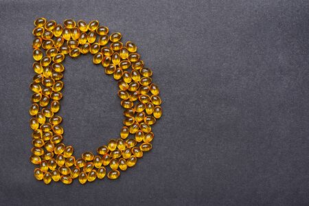 Vitamin D capsules laid out in the shape of the letter D on a black background. Health support and treatment.