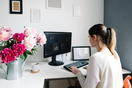 peonies in a garden watering can, a desktop in the home. woman at work