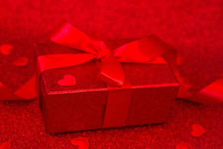 A gift box with a red bow on a red background with hearts. Valentine festival . copy space. Stock Photo