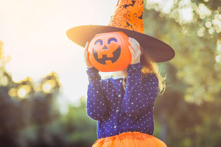 Halloween kids. Little girl with jack-o-lantern in witch hat with pumpkin candy bucket. Toddler kid with jack-o-lantern