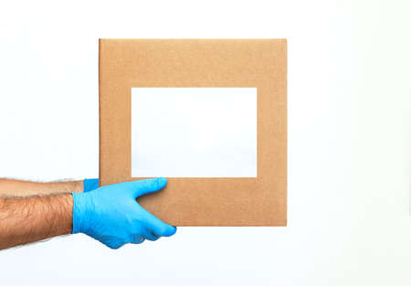 Delivery man holding cardboard boxes. Delivery by courier in medical rubber medical gloves. The shipping time during coronavirus