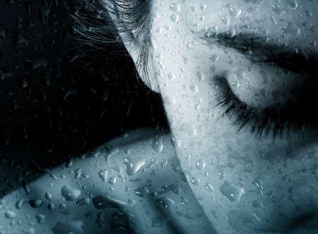 larmes: Photo d'une personne jeune femme derri�re la vitre avec les gouttes de pluie