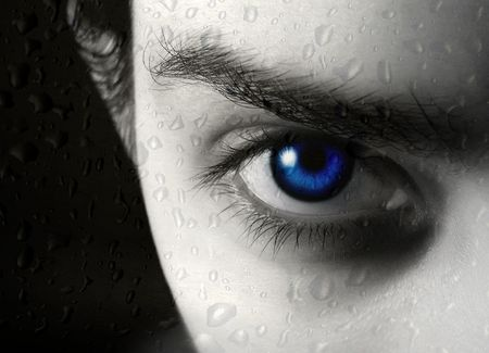 hypnosis: Photo of half of face of the beautiful young blue-eyed girl and drop of a rain on glass Stock Photo