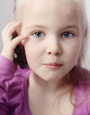 Little funny girls with telephone photo