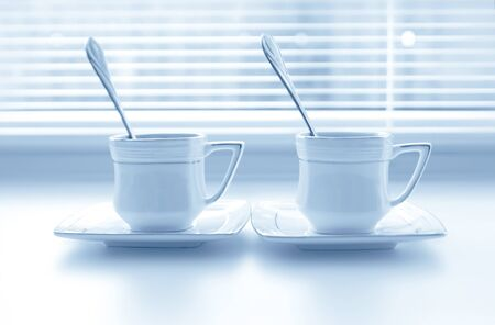 Two cups of coffee on the white windowsill with shutters photo