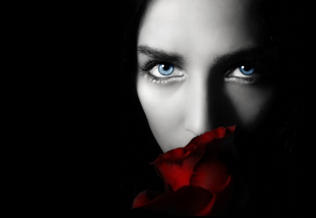 Portrait beauty young woman with rose on a black background photo