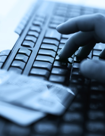 Tinted blue photo with computer keyboard, credit cards and hands Stock Photo - 13152043
