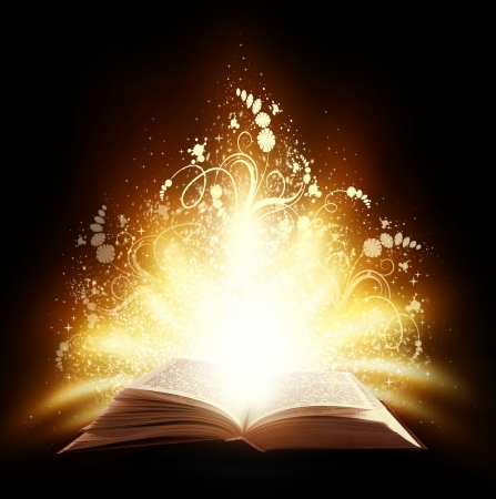 Magic open book with light and ornate on a black background Stock Photo