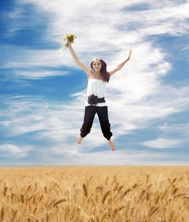 Beautiful Summer Landscape And Flying Young Woman With Bouquet Of Dandelions photo
