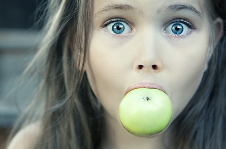 amazement: Surprised A Beautiful Little Girl With Green Apple In Her Mouth Stock Photo