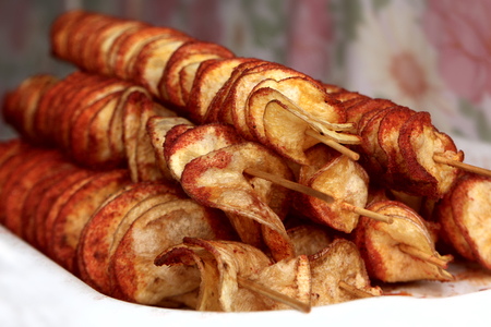 typical: Fried potato chips on wooden skewers close-up