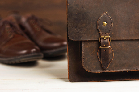 Men's fashion with brown leather shoes and business bag on a wooden background. Men's fashion, shoes, accessory, business background. Selective focus.