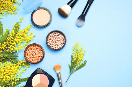 Set of decorative cosmetics for make-up Powder  Eyeshadow Corrector Brushes and flowers of mimosa on blue background. Makeup Accessories Top view