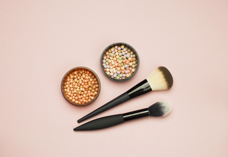 Set of colorful cosmetics Powder  Corrector Brushes on pink background. Makeup Accessories Top view
