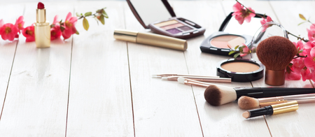 Various cosmetic products for make-up with pink flowers on a white wooden background with copy space. Make-up, lipstick, mascara, eye shadow, powder, brushes Stock Photo