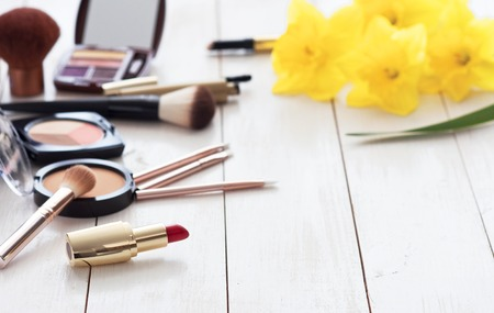 Various cosmetic products for make-up with yellow daffodils on a white wooden background with copy space. Make-up, lipstick, mascara, eye shadow, powder, brushes