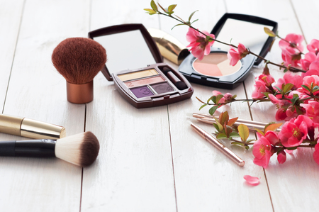 Various cosmetic products for make-up with pink flowers on a white wooden background with copy space. Make-up, lipstick, mascara, eye shadow, powder, brushes