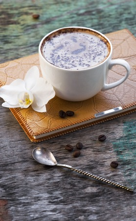 A cup of hot coffee and an orchid flower with a diary on a wooden background. Traditional drink of cappuccino or cocoa Wooden background Orchid Notepad Diary Autumn drink