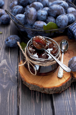 Homemade plum jam in a glass jar and fresh blue plums in a bowl on a dark rustic wooden background with copy space top view. Fruits, vitamins, food background 版權商用圖片
