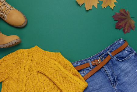 Female orange knitted sweater, blue jeans, boots and autumn leaves on green background top view flat lay Fashion Lady Clothes Set Trendy Cozy Knit Jumper Autumn accessories Female fashion look 스톡 콘텐츠