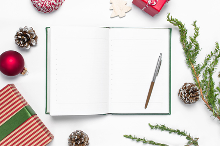 Open notebook with blank pages, gift boxes, fir branches on white background flat lay top view. Christmas planning concept Holiday decorations 2019 Goals. New Year, Christmas, winter decoration Stock Photo