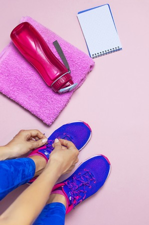 Young woman in sporting blue leggings laces sneakers, preparing for training. Accessories for sports bottle of water towel notebook on pastel pink background flat lay top view. Fitness concept