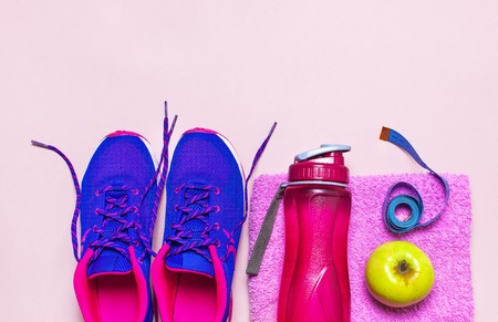 Fitness concept with Ultra violet pink female sneakers, water bottle, pink towel, apple on pastel pink background flat lay top view. Sports shoes, fitness concept of healthy lifestile.