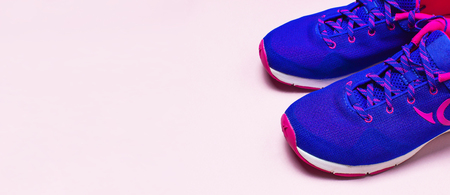 Ultra blue violet pink female sneakers on pastel pink background flat lay top view with copy space. Sports shoes, fitness, concept of healthy lifestile everyday training.