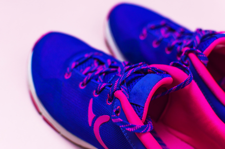 Ultra blue violet pink female sneakers on pastel pink background flat lay top view with copy space selective focus. Sports shoes, fitness, concept of healthy lifestile everyday training.