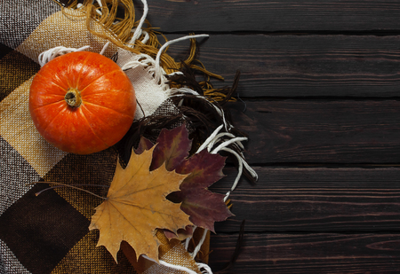 Orange pumpkin, autumn colorful leaves and checkered plaid on a dark wooden background top view with space for text Autumn Pumpkin Thanksgiving Background. Stock Photo