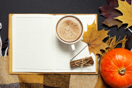 Opened notebook, pumpkin, cup of pumpkin cocoa or coffee, cinnamon, yellow autumn maple leaf, checkered plaid on black background top view copy space. Autumn flat lay background. Autumn, fall halloween concept.