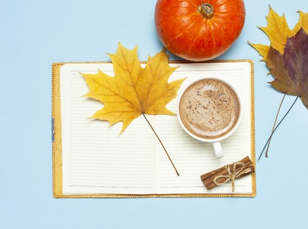 Opened notebook, orange pumpkin, pumpkin spiced latte or coffee in cup, cinnamon, yellow autumn maple leaf on blue background top view flat lay. Autumn or winter hot drink halloween concept.