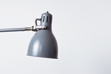 A gray table lamp in the interior against a white wall. The concept of business or education with a place for your text. Detail of interior minimalism background. Banco de Imagens