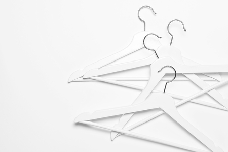 White wooden hangers isolated on white background top view. Store concept, sale, design, empty hanger Place for text.