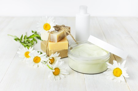 Opened plastic container with cream, handmade soaps, white cosmetic bottle containers and chamomile flower on a white background. Herbal dermatology cosmetic Spa concept organic cosmetic Natural beauty product Stock Photo