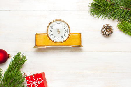 New Year or Christmas background. Retro alarm clock pine branches cones gifts presents toys red ball on white wooden background top view with copy space Christmas timer Time to celebrate Xmas 免版税图像