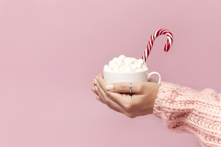 Female hands in knitted sweater holding cup of marshmallows and Christmas candy cane on pink background Flat Lay copy space Winter traditional food Festive decor celebration presents Xmas holiday. Stock Photo
