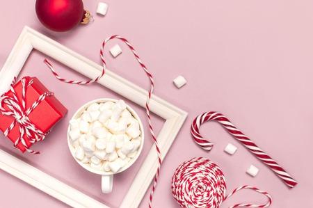 Weißer Becher mit Marshmallows Candy Cane Geschenkboxen roter Ball Verpackung Spitze Fotorahmen auf rosa Hintergrund Draufsicht Flache Lage Winter traditionelles Getränk Essen. Festliche Dekoration Feier Weihnachten Neujahr Urlaub
