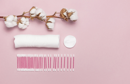 Spa concept. Flat lay background with cotton branch, cotton pads, eared sticks. Cotton Cosmetic Makeup Removers Tampons Hygienic sanitary swabs on the pink background Top view with space for text