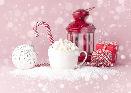 White mug with marshmallows Candy Cane gifts boxes Christmas New Year ball packaging lace flashlight in the snow on pink background Flat Lay. Winter traditional drink food Festive decor celebration