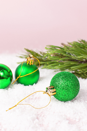 Green Christmas New Year balls in the snow and pine branches on pink background Flat Lay copy space. Holiday Baubles, beautiful Decoration Festive decor celebration Xmas holiday greeting card Banco de Imagens
