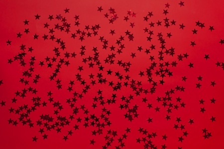 Red holographic glitter confetti in the form of stars on red background Flat lay top view copy space. Festive holiday pastel backdrop. Birthday, congratulations, Christmas New Year