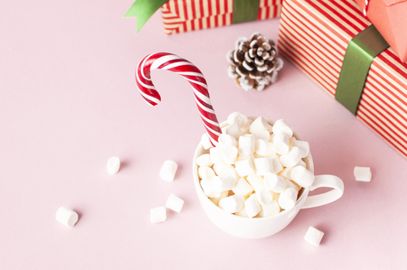 White mug with marshmallows Candy Cane gifts boxes with green ribbon on pink background Flat Lay Winter traditional drink food Festive decor Christmas New Year presents Xmas holiday.