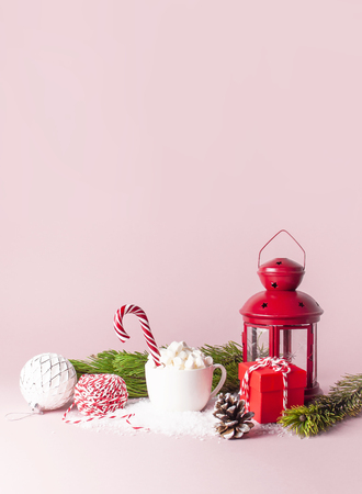 White mug with marshmallows Candy Cane, gifts boxes pine branches Christmas New Year ball packaging lace flashlight in the snow on pink background Flat Lay Winter traditional drink food Festive decor